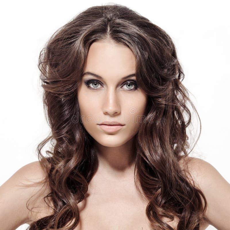 Härlig brunettkvinna. Lockigt långt hår. arkivfoto