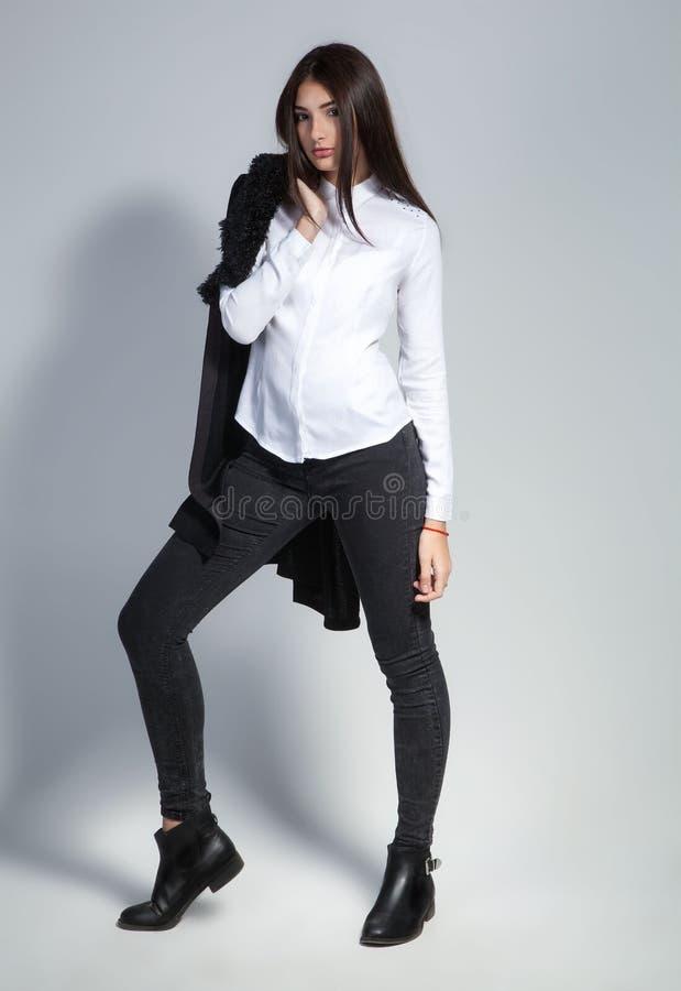 Härlig brunettkvinna med älskvärt långt hår som poserar i en vit skjorta och jeans i en studio bedsheetmode lägger förföriskt vit royaltyfria bilder