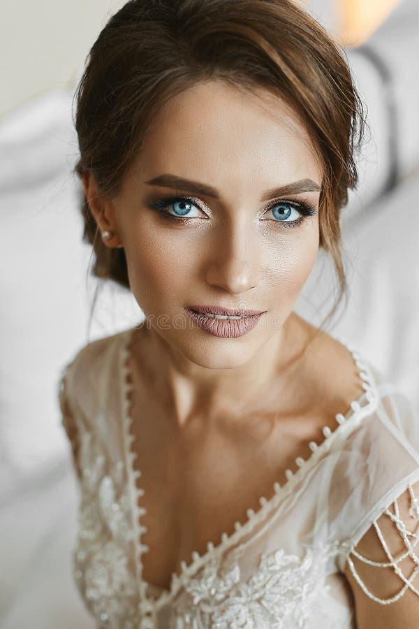 Härlig brunettkvinna med att gifta sig frisyren, med ljus makeup och med djupblå ögon Stående av det ungt arkivfoto