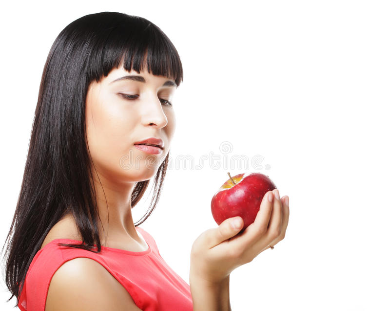 Härlig brunettkvinna med det röda äpplet i händer royaltyfri bild