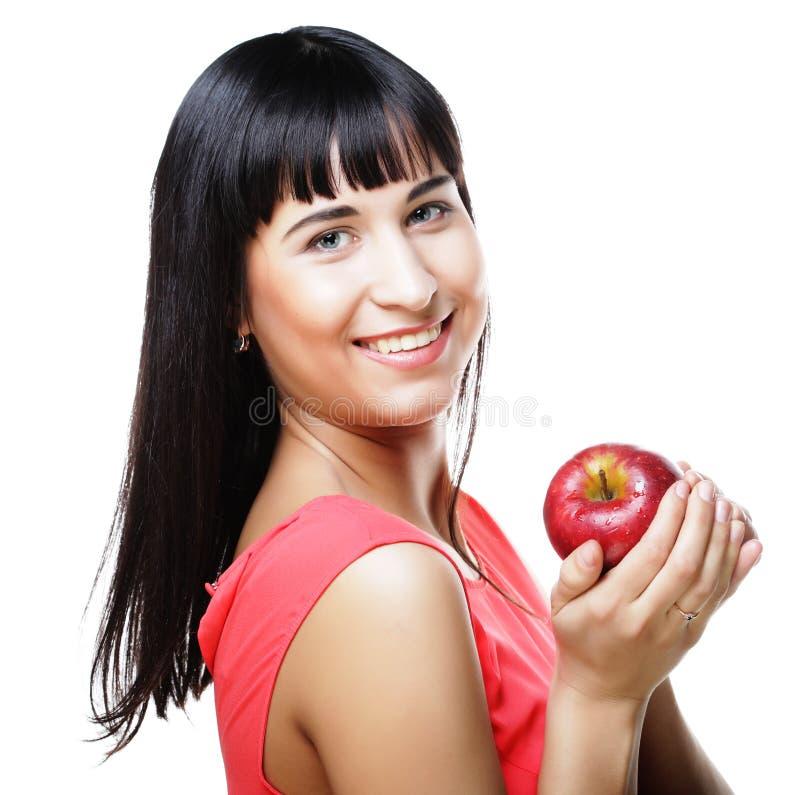 Härlig brunettkvinna med det röda äpplet i händer royaltyfria bilder