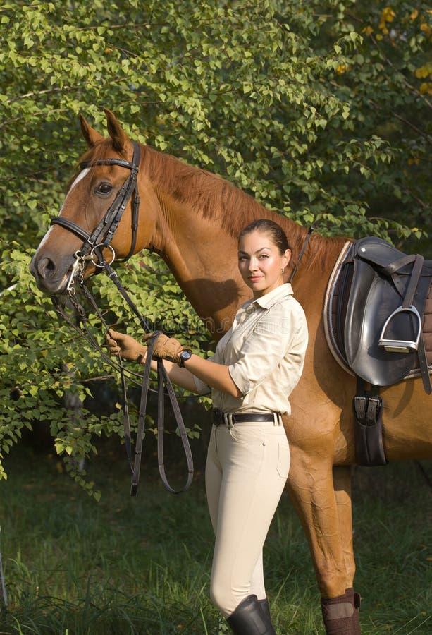 Härlig brunettkvinna med en brun häst arkivbild