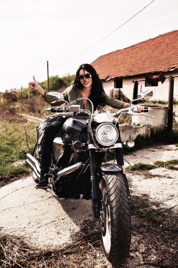 Härlig brunettkvinna med en klassisk motorcykel c royaltyfri bild