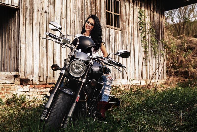 Härlig brunettkvinna med en klassisk motorcykel c arkivbilder
