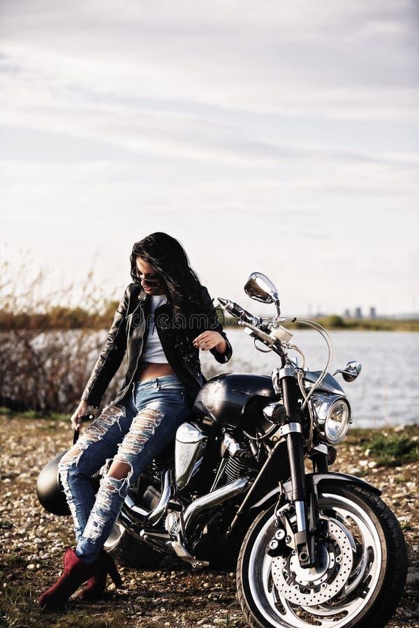 Härlig brunettkvinna med en klassisk motorcykel c royaltyfria bilder