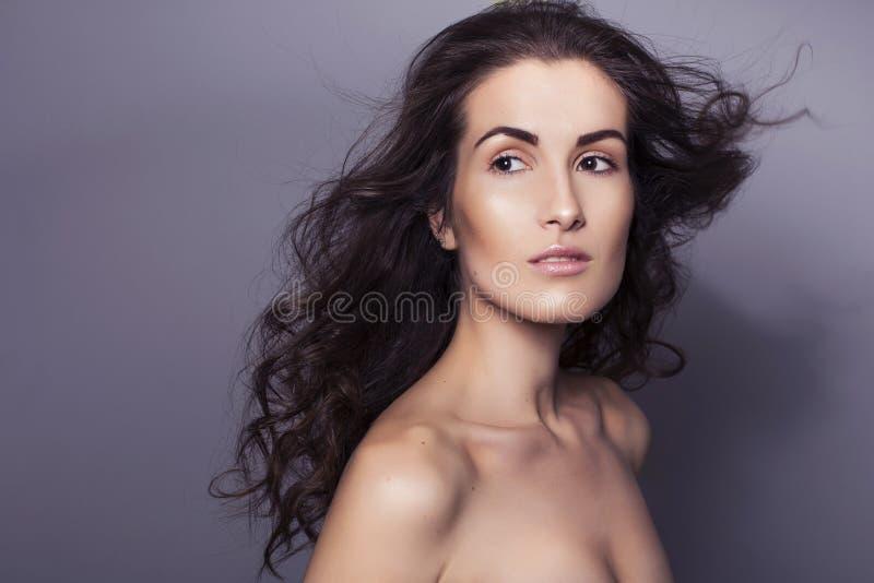 Härlig brunettkvinna med klar ny hud och lockigt hår på fotografering för bildbyråer