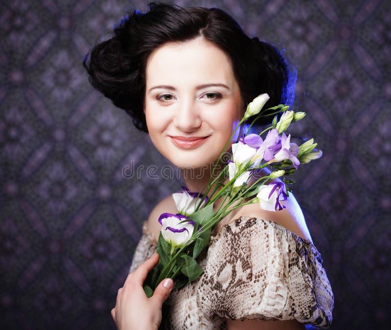 Härlig brunettkvinna med lila blommor royaltyfri bild