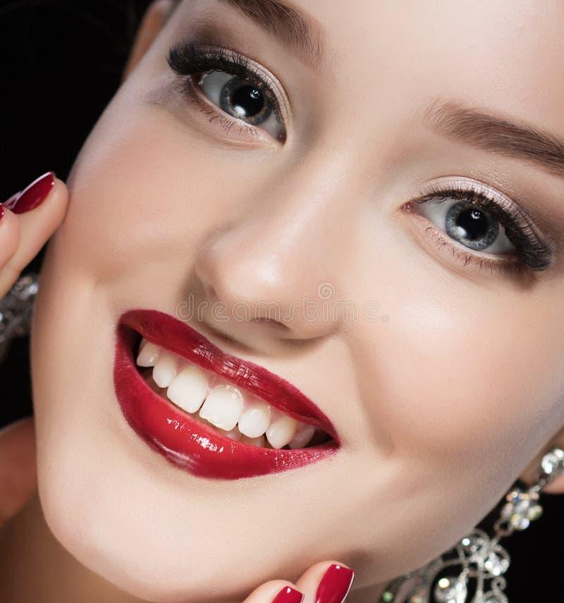 Härlig brunettkvinna med ljusa smink- och smyckenörhängen som ler närbild Röda kanter och spikar, aftonsminket arkivbild