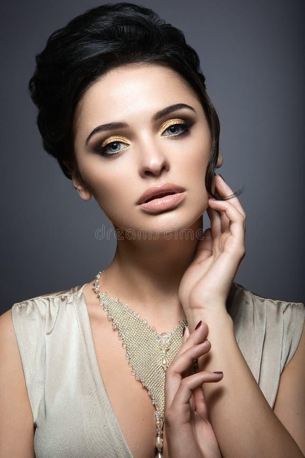 Härlig brunettkvinna med perfekt hud, guld- makeup och handgjorda smycken Härlig le flicka royaltyfria bilder