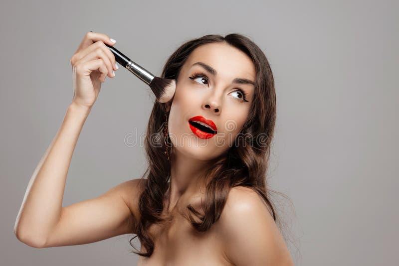 Härlig brunettkvinna med röd läppstift på kanter Närbildflicka med härligt smink royaltyfria bilder