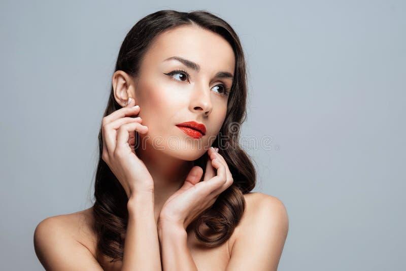 Härlig brunettkvinna med röd läppstift på kanter Närbildflicka med härligt smink royaltyfria foton