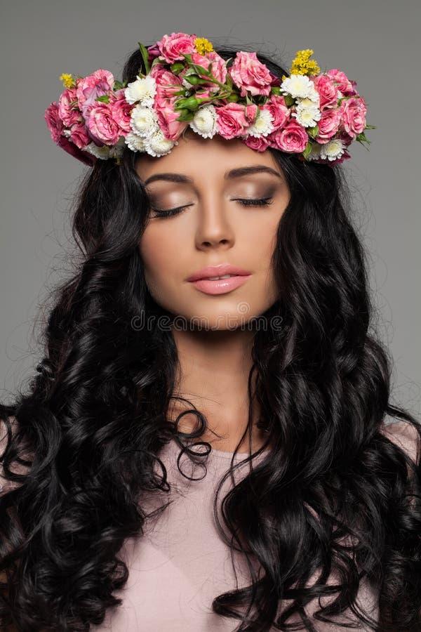 Härlig brunettkvinna med sommarblommor arkivfoto