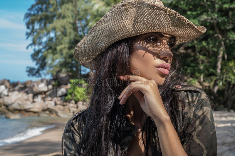 Härlig brunettkvinna med sugrörhatten och solglasögon i tropisk skog royaltyfri bild