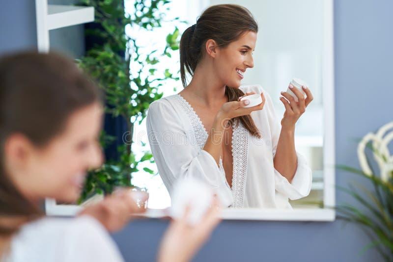 Härlig brunettkvinna som applicerar framsidakräm i badrummet royaltyfria foton
