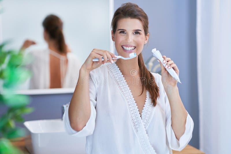 Härlig brunettkvinna som borstar tänder i badrummet arkivfoto