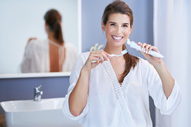 Härlig brunettkvinna som borstar tänder i badrummet fotografering för bildbyråer