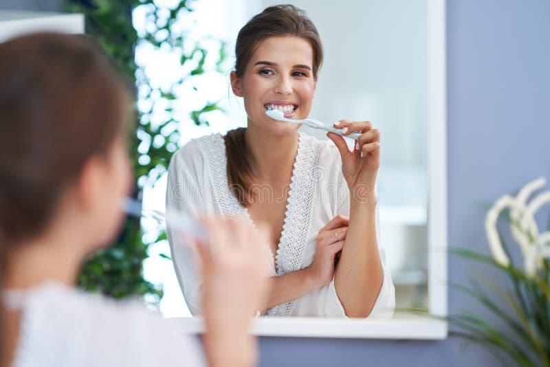 Härlig brunettkvinna som borstar tänder i badrummet arkivbilder