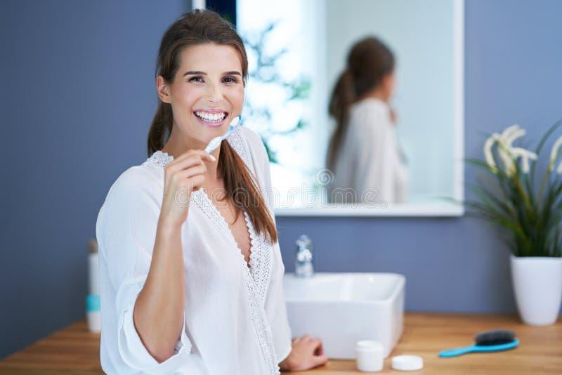 Härlig brunettkvinna som borstar tänder i badrummet royaltyfria bilder