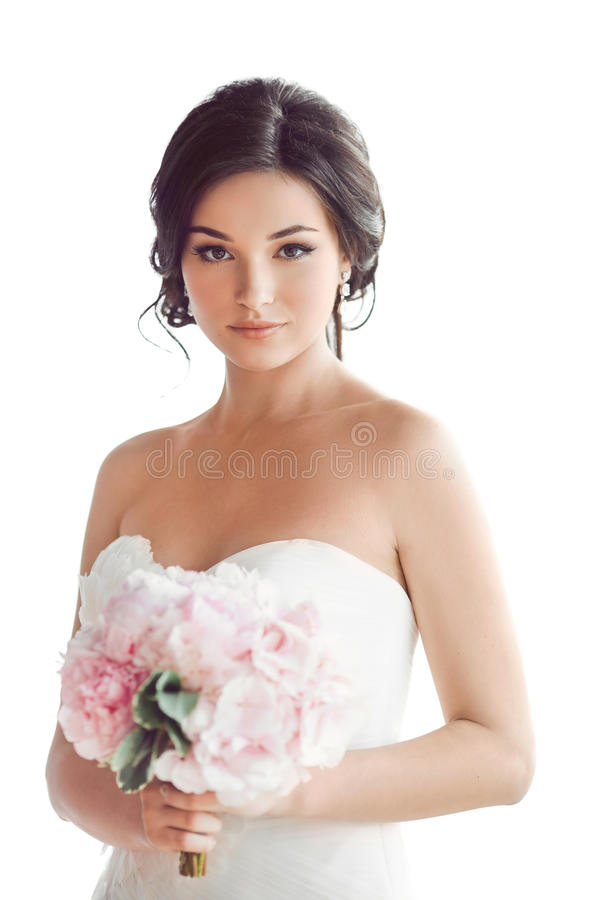 Härlig brunettkvinna som brud med den rosa bröllopbuketten på vit royaltyfri foto