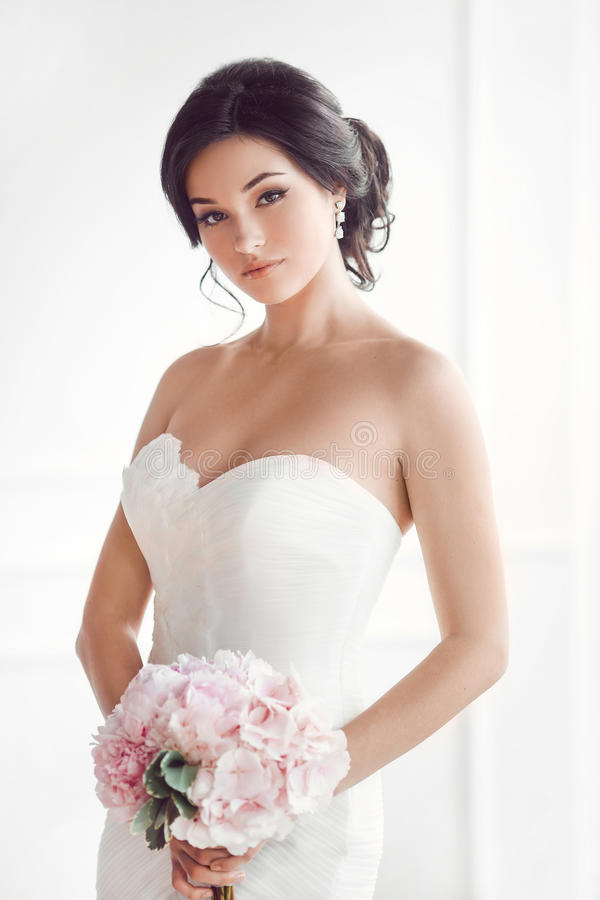 Härlig brunettkvinna som brud med den rosa bröllopbuketten på vit royaltyfria foton