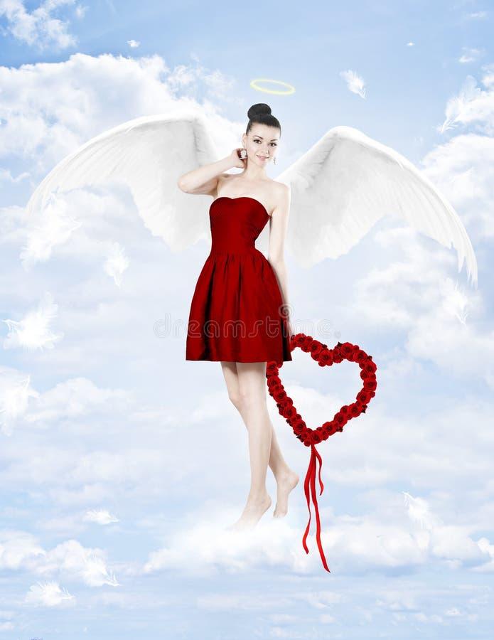 Härlig brunettkvinna som kupidon med hjärta som göras av rosor arkivbild