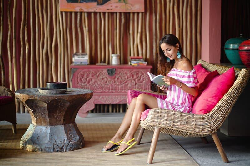 Härlig brunettkvinna som sitter på en rosa soffa och läser en bok och le Inre i etnisk stil arkivfoton