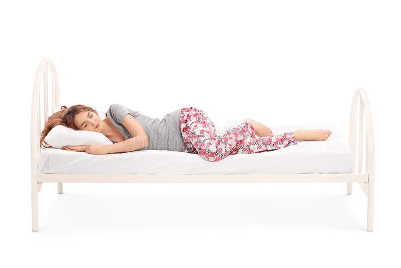 Härlig brunettkvinna som sover i en säng arkivfoton