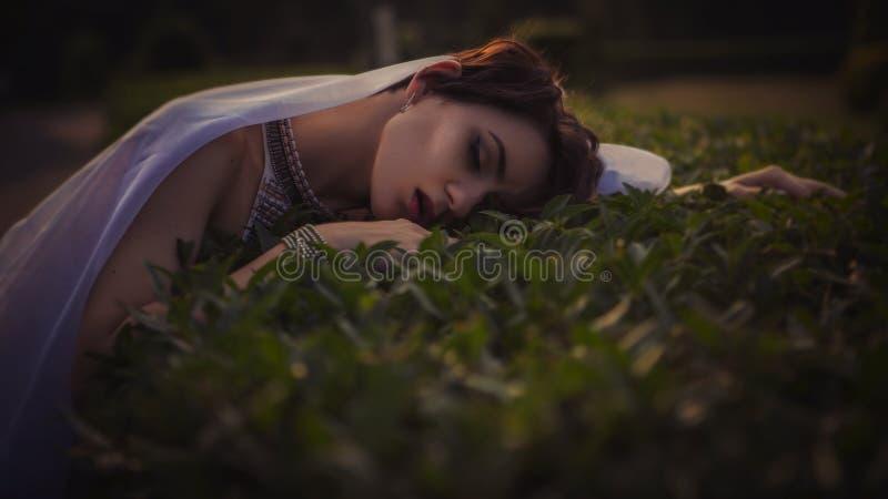 Härlig brunettkvinna som sover i ett gräs och blommor i royaltyfri foto