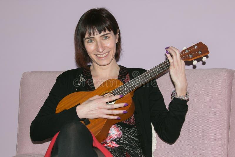Härlig brunettkvinna som spelar ukulelet royaltyfri foto