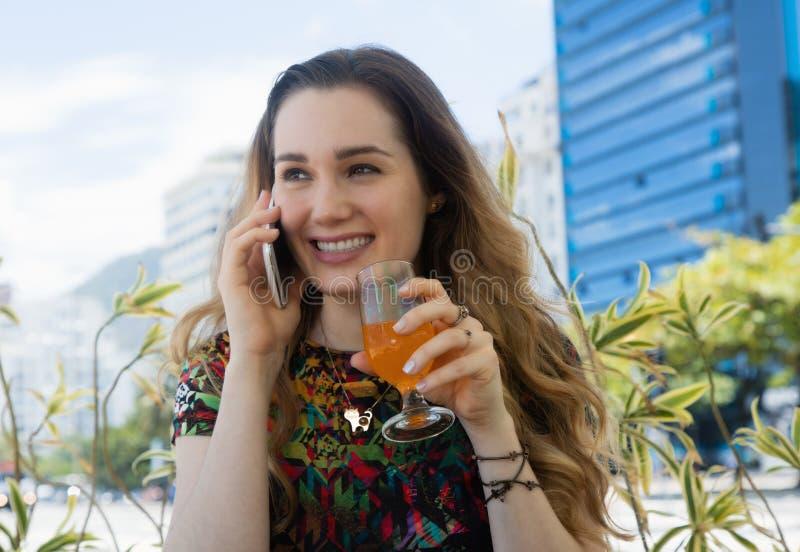 Härlig brunettkvinna som talar på mobiltelefonen i restaurang arkivbilder