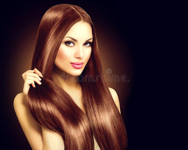 Härlig brunettkvinna som trycker på hennes långa hår