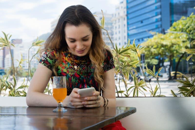 Härlig brunettkvinnamessaging i restaurang arkivfoto