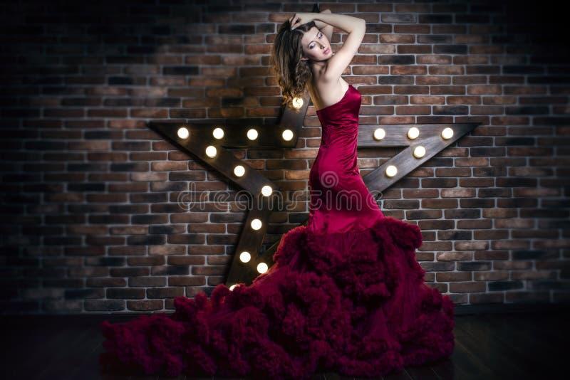 Härlig brunettkvinnamodell i lyxig röd klänning royaltyfria foton