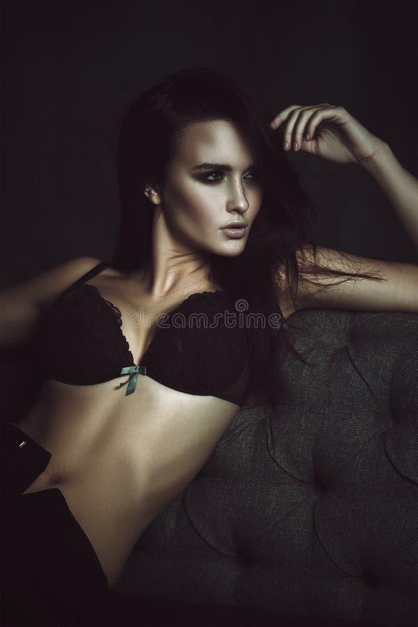 Härlig brunettkvinnaVogue stil på soffan royaltyfria bilder