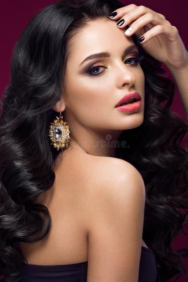 Härlig brunettmodell: krullning, klassisk makeup, guld- smycken och röda kanter Skönhetframsidan royaltyfria foton