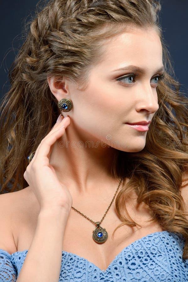 Härlig brunettmodellflicka med långa lockigt hår och smycken e arkivfoton