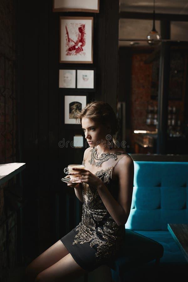 Härlig brunettmodellkvinna med blåa ögon och perfekt kropp i svart och guld- coctailklänning med en kopp kaffe in fotografering för bildbyråer