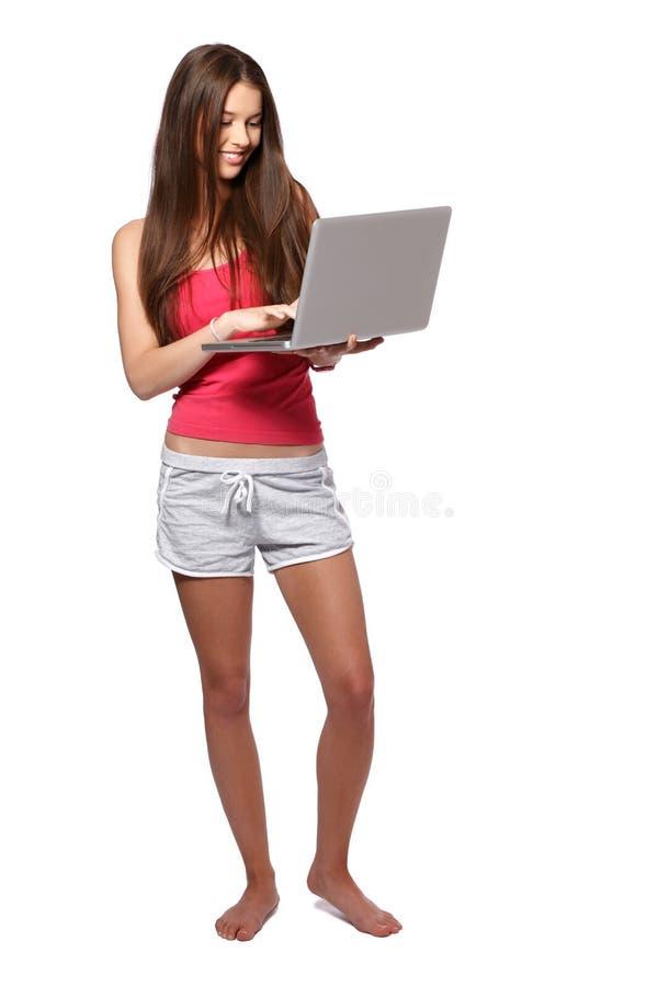 Härlig brunetttonåringflicka med bärbar dator som isoleras på vit arkivfoton