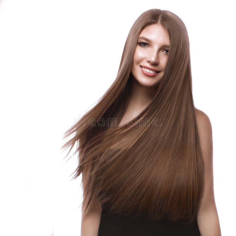 Härlig brunhårig flicka i flyttning med ett perfekt slätt hår och klassiskt smink Härlig le flicka arkivbilder