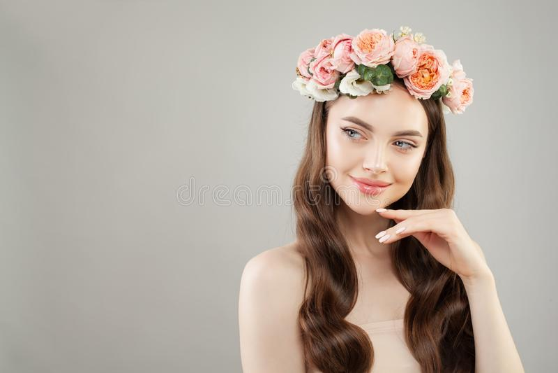 Härlig brunnsortkvinna som åt sidan ser Perfekt modell med klar hud, långt brunt hår och blommor arkivfoto