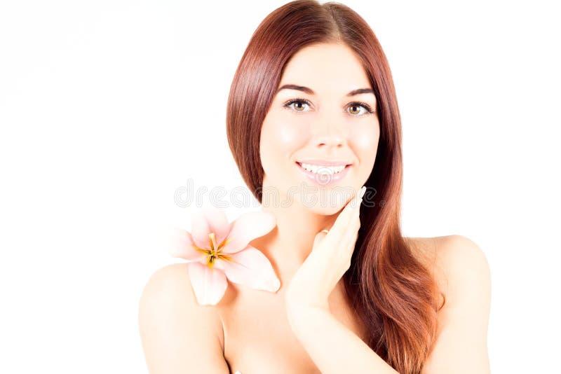 Härlig brunnsortkvinna som trycker på hennes hals Kvinnan med rosa färger blommar att le med vita tänder Kvinna med ny och klar h royaltyfri bild