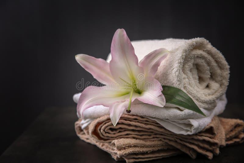 Härlig brunnsortsammansättning med handdukar och liljan blommar royaltyfria bilder