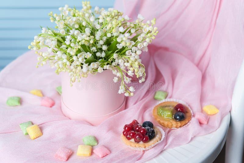 Härlig bukett av blommor i en rund hattask på en tabell royaltyfria foton