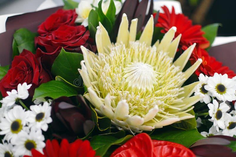 Härlig bukett av blommor i en stilfull hattask arkivfoton