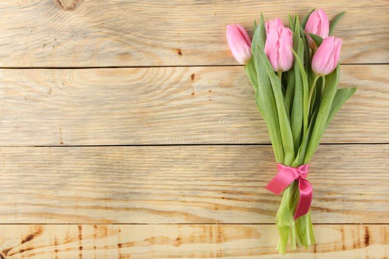Härlig bukett av blommor av rosa tulpan på en naturlig träbakgrund placera text Top beskådar Vår ferier arkivbild