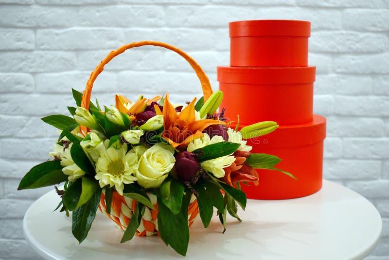 Härlig bukett av färgrika blommor i orange korg arkivfoto