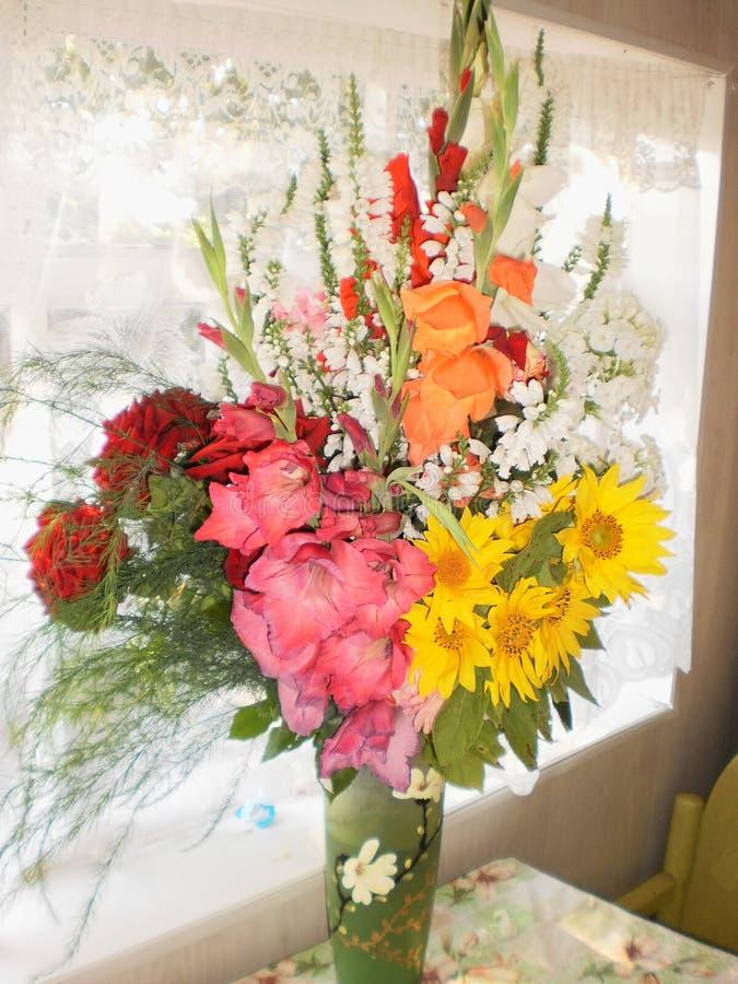 Härlig bukett av gladioli, rosor och blommor av en solros, en vas av blommor royaltyfria bilder