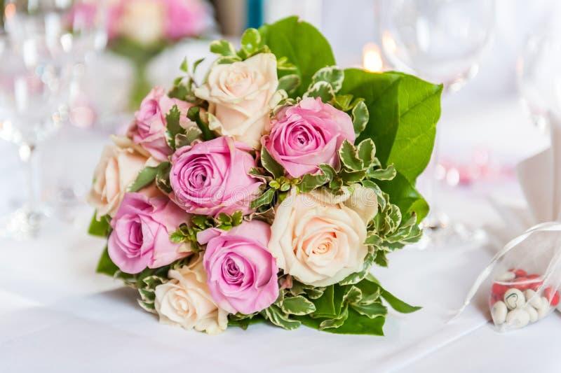 Härlig bukett av gula och rosa rosor på den dekorerade tabellen royaltyfri foto