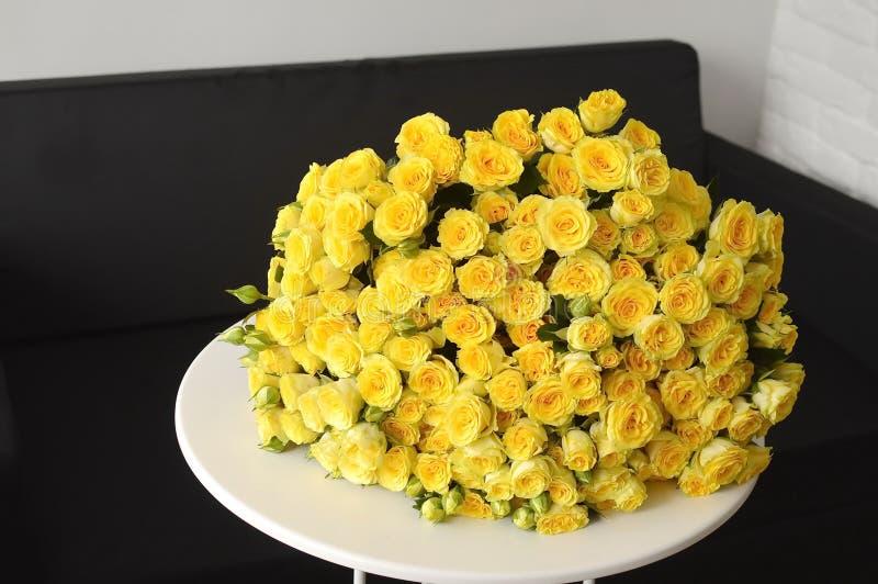 Härlig bukett av gula rosa buskar på en vit tabell royaltyfria foton