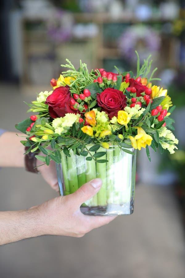 Härlig bukett av röda rosor, gul freesia och andra blommor i de manliga blomsterhandlarehänderna royaltyfri fotografi